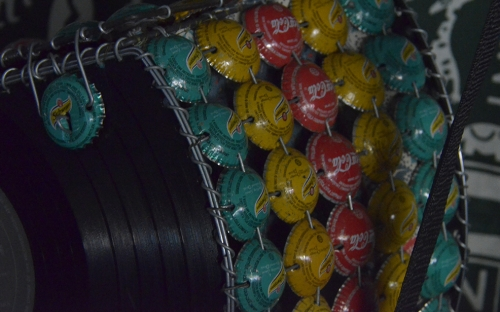 A bag made from bottle tops, wire and old vinyl disc