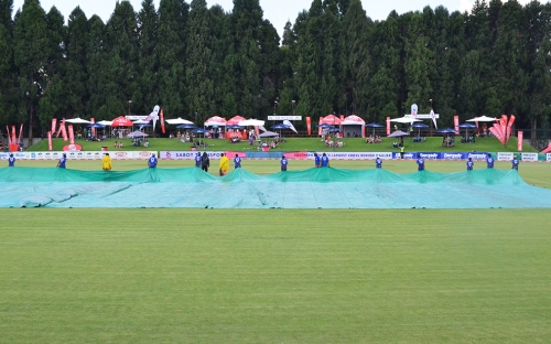 Groundsmen running onto the pitch with the covers